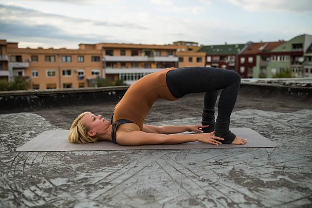 Yoga-Setu Bandha Sarvangasana/Supported Bridge Pose Beautiful woman practicing yoga on the roof. shoulder stand stock pictures, royalty-free photos & images