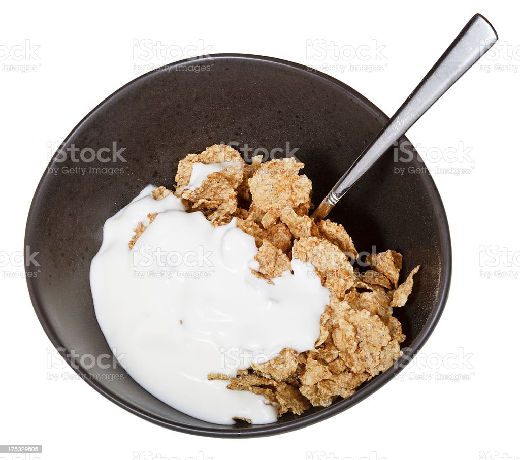 yoghurt and spoon into bowl of cereal royalty-free stock photo