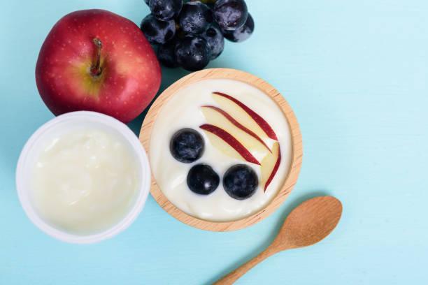 Joghurt mit in Scheiben geschnittenem Apfel und Trauben in einer Schüssel – Foto