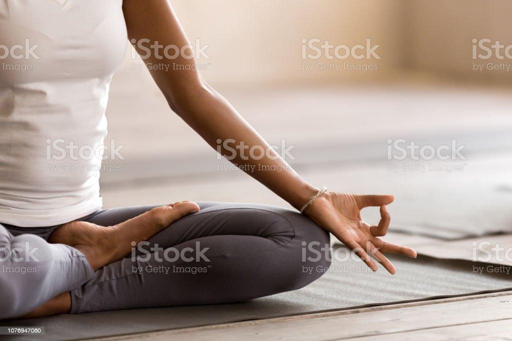 Yogi zwarte vrouw het beoefenen van yoga les, doen Ardha Padmasana oefening - Royalty-free Ademhalingsoefening Stockfoto