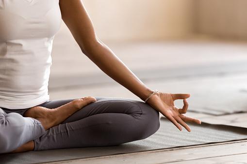 Yogi black woman practicing yoga lesson, doing Ardha Padmasana exercise