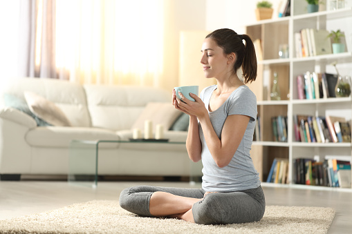 Shot of a young woman listening to music while meditating at home