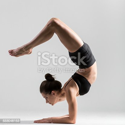 Beautiful sporty yogi girl practices yoga asana, pincha mayurasana, forearm stand,  feathered peacock pose, elbow balance