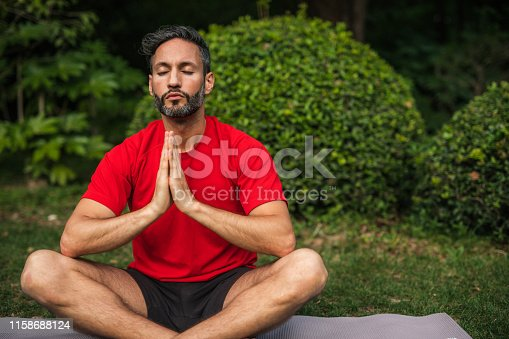 One young couple man in sport clothing sitting on exercise mat and meditating.