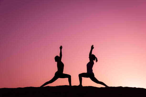 Yogi silhouettes on virabhadrasana on top of Maspalomas sand dunes at colorful sunset stock photo