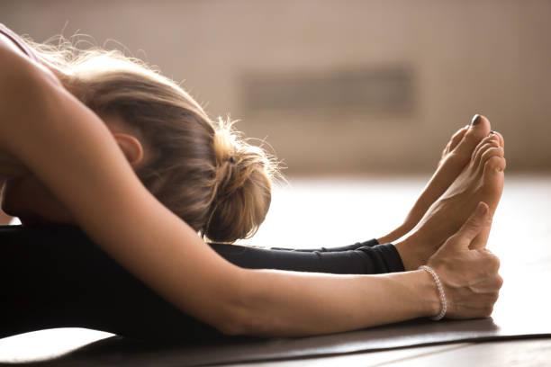 yogi-junge frau paschimottanasana übung, nahaufnahme - yin yoga stock-fotos und bilder