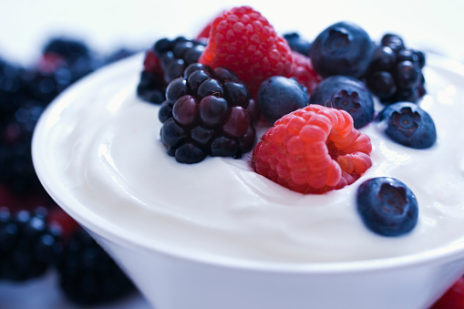 Yogurt with Blueberries, Blackberries, Raspberries. Selective focus,on a white background.