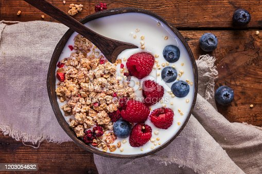 A healthy breakfast yogurt meal with granola,  puffed quinoa and fresh blueberries and raspberries. There meal is in a natural coconut bowl with a linen napkin on the rustic wooden table.