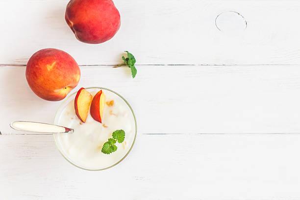 yogurt dessert with peaches, flat lay, top view - pfirsich milchshake stock-fotos und bilder