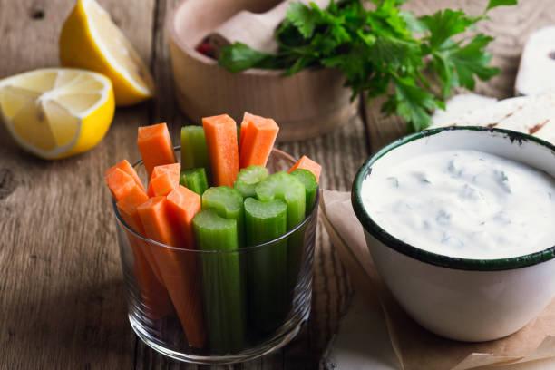 Joghurt-Dip mit Petersilie serviert auf rustikal mit Tortilla-Chips und frischem Gemüse – Foto
