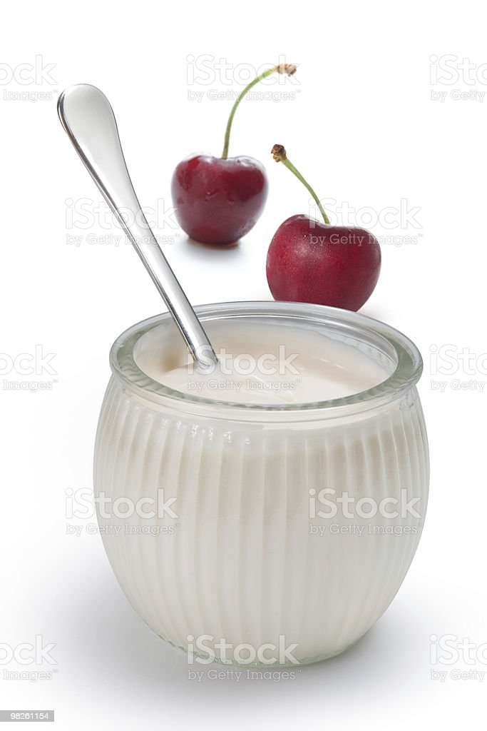 Yogurt in a glass jar with spoon and cherries royalty-free stock photo