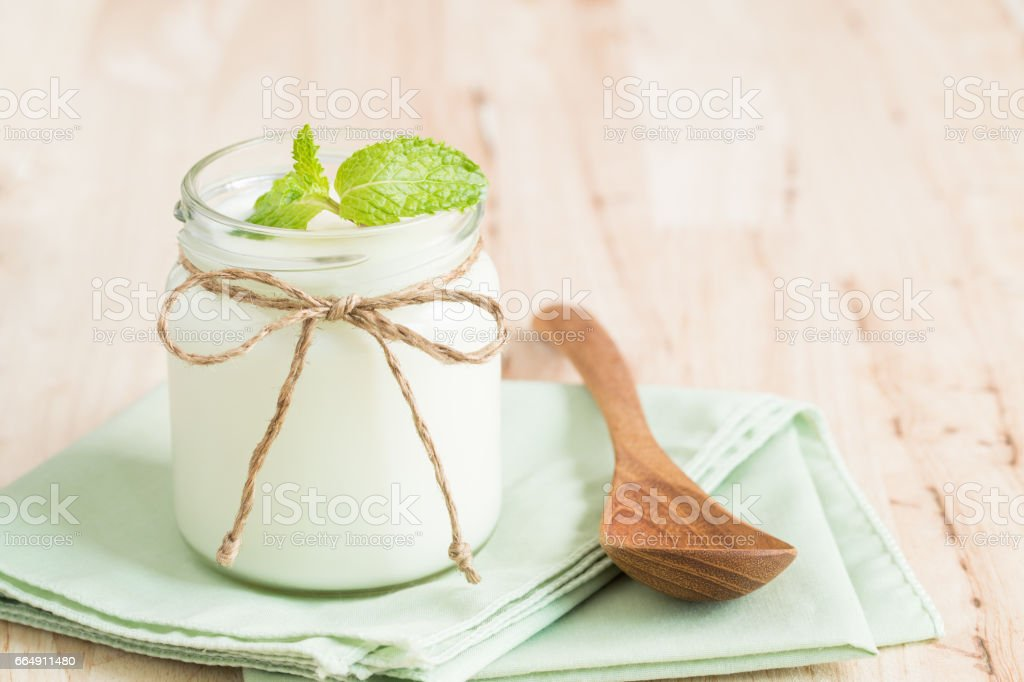 Yogurt in glass bottles on wooden table stock photo