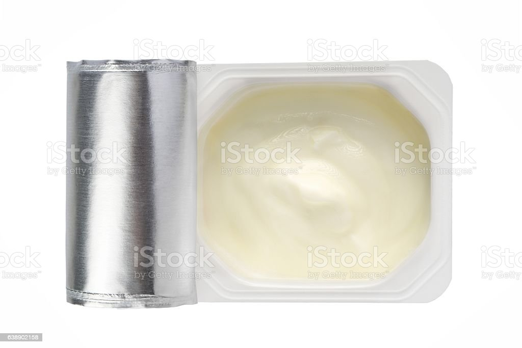 Yogurt in white plastic pot from above on white background stock photo