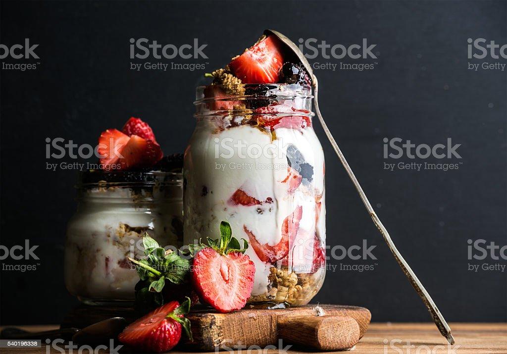 Yogurt oat granola with strawberries, mulberries, honey and mint leaves stock photo