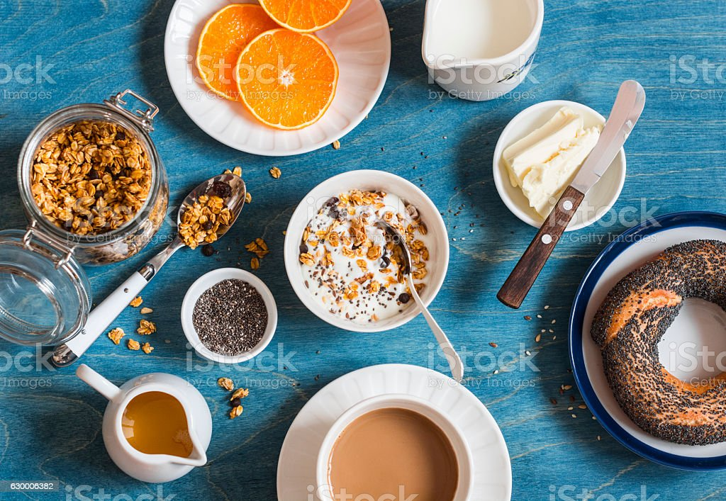 Yogurt, pumpkin granola, bagel, butter on a blue table. Breakfast stock photo