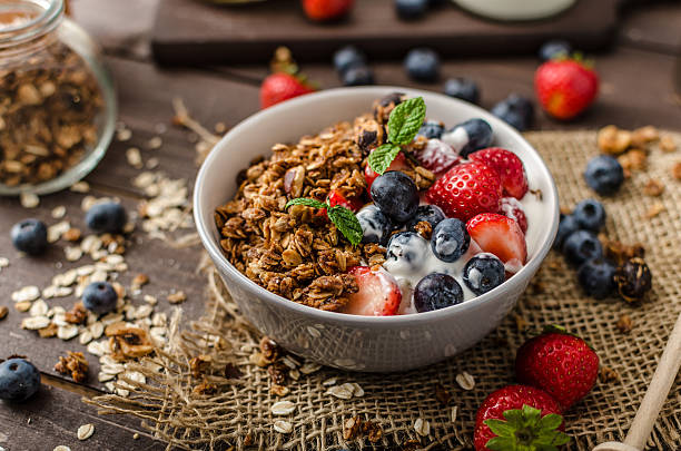 Yogurt with baked granola and berries in small bowl stock photo