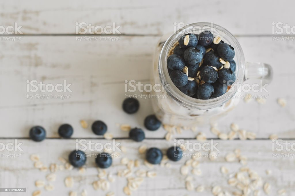 Yogurt with bluberries and oats, top view. Overnight oats in a glass jar on wooden table. Healthy ans easy breakfast recipe stock photo