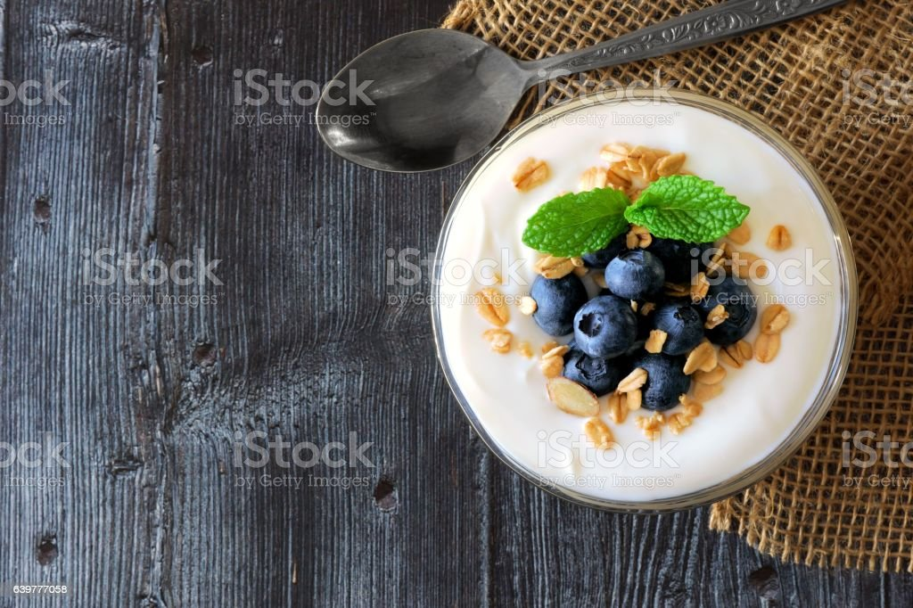 Yogurt with blueberries, granola, above view on rustic dark wood stock photo