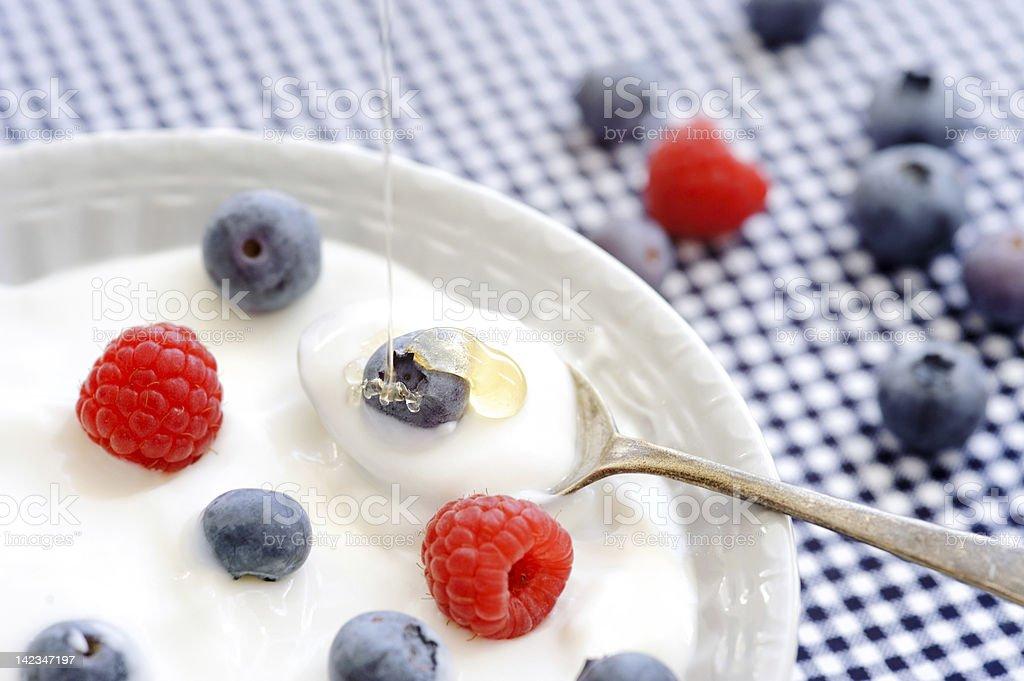 Yogurt with fresh berries and honey served in white bowl stock photo