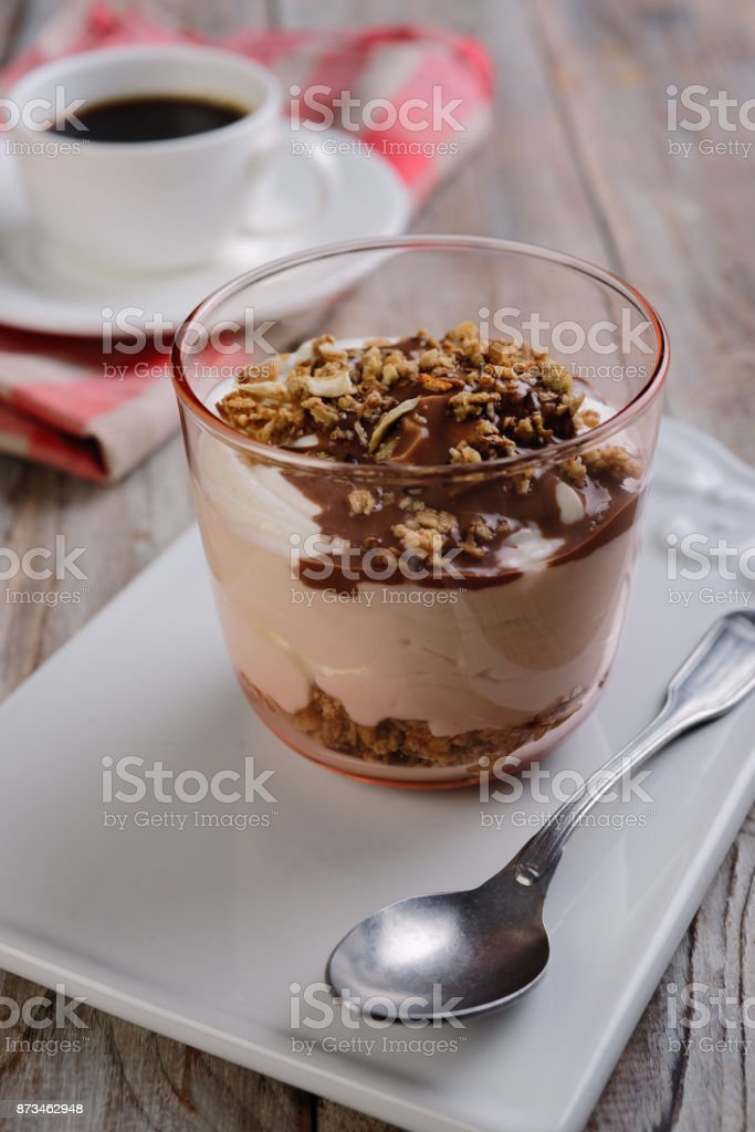 Yogurt with granola under chocolate sauce and a cup of black coffee...