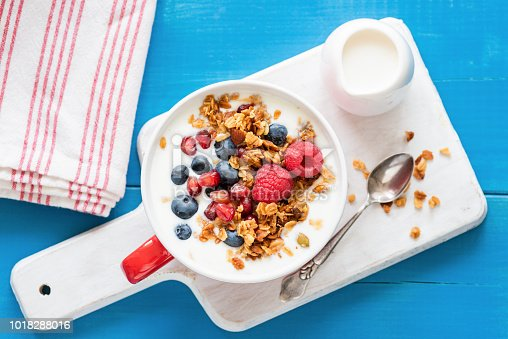 599887760 istock photo Yogurt with pomegranate seeds, fruits and breakfast cereals 1018288016
