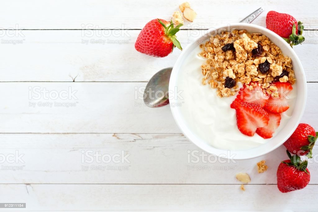Yogurt with strawberries & granola, flat lay, side orientation over white wood.