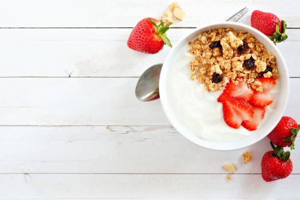 Yogurt with strawberries & granola, flat lay, side orientation over white wood. stock photo