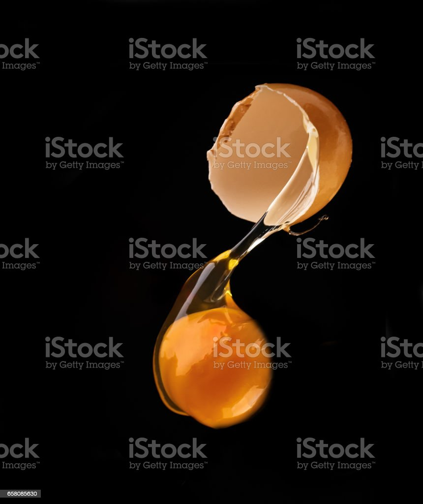 Yolk dropping from cracked raw egg divided royalty-free stock photo