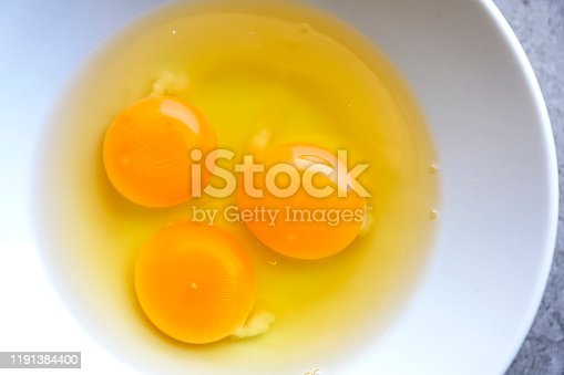 Raw organic egg yolk in white bowl background
