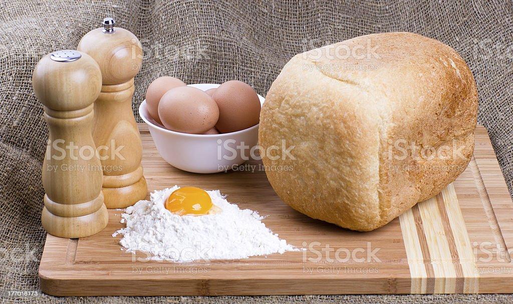 Yolk, eggs, salt, pepper and fresh hot home-made bread stock photo