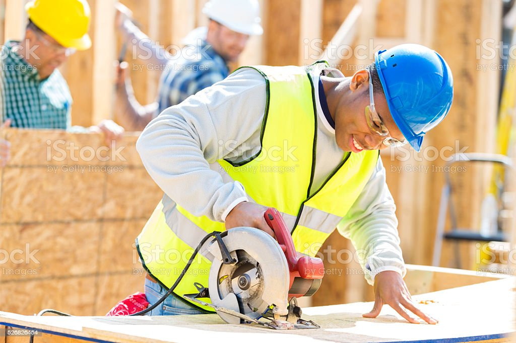Yong African American man uses power tool at construction site stock photo