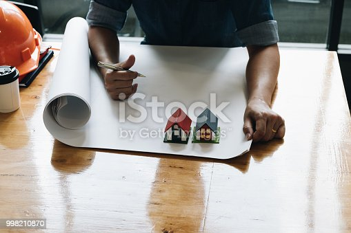 istock Yong architect man working with blueprints and small house model safety helm and coffe cup ,yong engineer inspection in workplace for architectural plan project,sketching a construction project ,Business concept 998210870