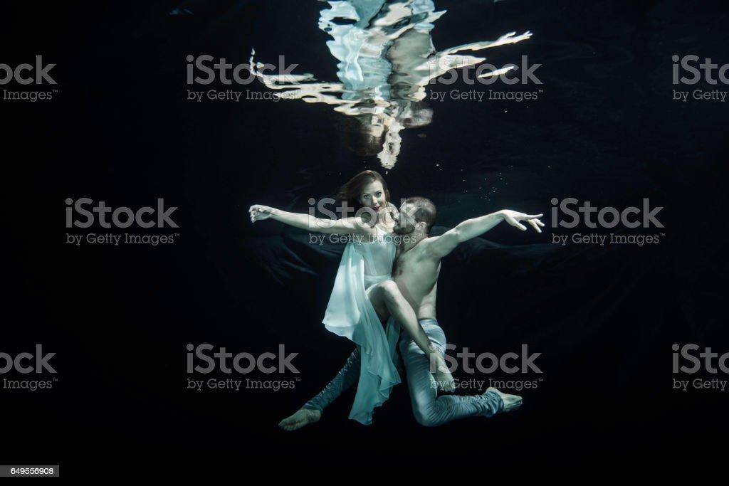 Yong couple of ballet dancers dacing underwater stock photo