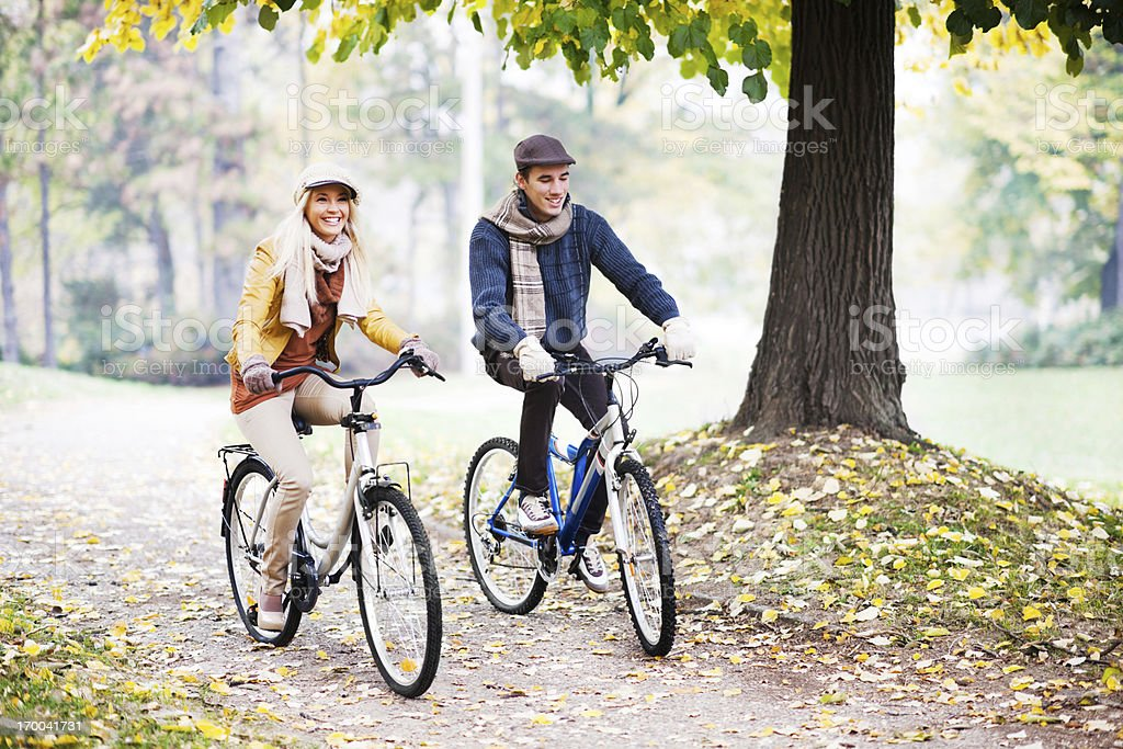 Yong couple rides bikes on a beautiful autumn day royalty-free stock photo