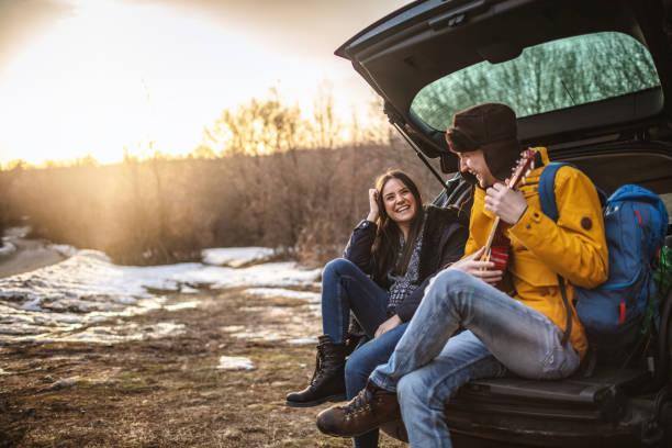 Yong Paar mit Gitarre im Kofferraum – Foto