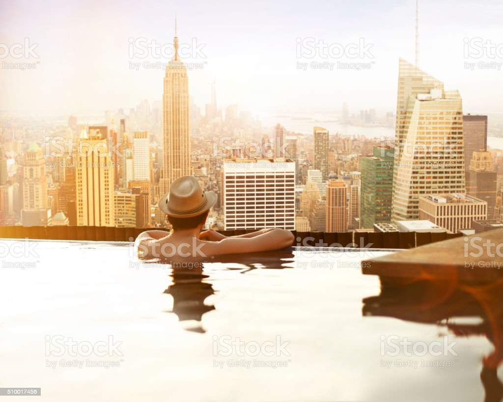Yong man relaxing on hotel rooftop stock photo