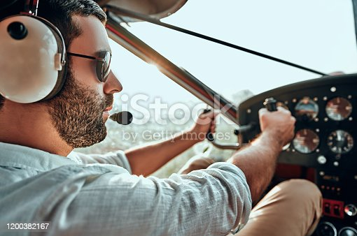 Yong man with beard in an airplane cabin flying a plane. Side view. Close up view