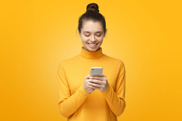 Yong pretty female standing isolated on yellow background looking at screen of phone, smiling nicely while chatting Yong pretty female standing isolated on yellow background looking at screen of phone, smiling nicely while chatting female likeness stock pictures, royalty-free photos & images