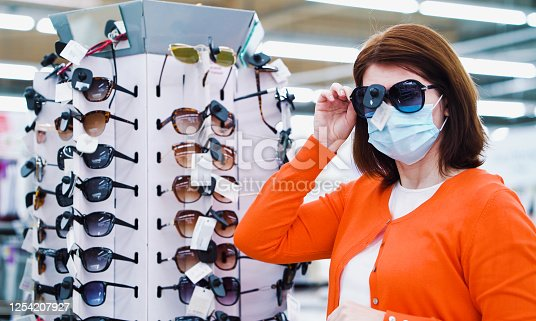 Young woman in medical mask trying on sunglasses in supermarket. Side view of customer buying accessories for vacation after COVID pandemic. Concept of shopping