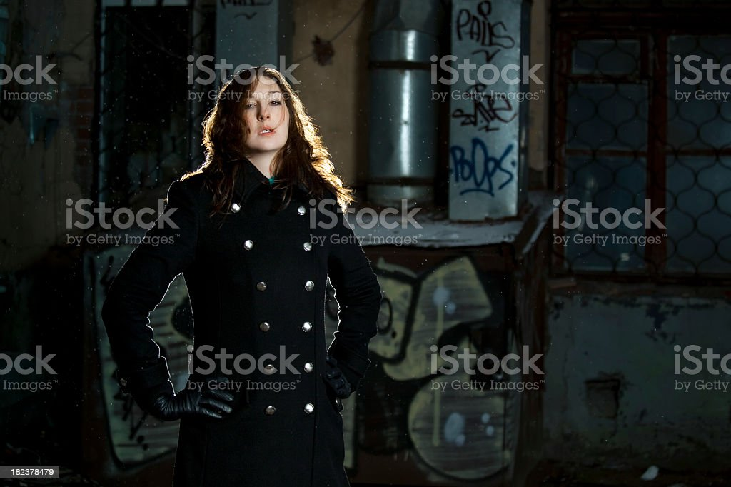 Yong woman standing on back street stock photo