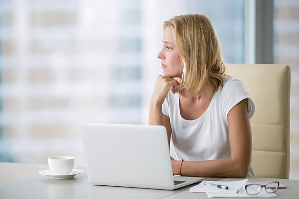 yong woman with laptop looking at the window - day dreaming stock photos and pictures