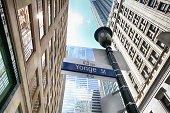 Toronto, Ontario, Canada - July 1, 2014: High-rise office buildings and a light pole with Yonge Street sign on it in the downtown Toronto, Canada (taken from below)