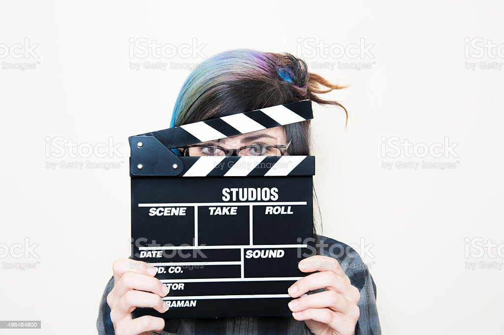 Yopung woman with clapper board on face stock photo