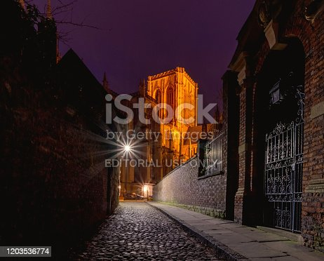 York, UK. January 31, 2020.  A section of York Minster at night with its medieval gothic architecture and central tower from a nearby street.  A metal gate is in the foreground.