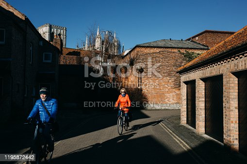 York, UK - February 3, 2018: An older man and woman ride a bike through the streets of York