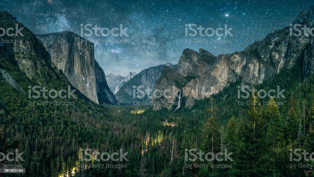Yosemite illuminated by waxing crescent moonlight with rising Milky Way. stock photo