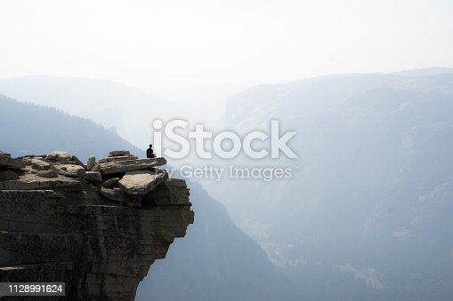 Hiker admires the smokey views of Yosemite Valley, seen from the Half Dome
