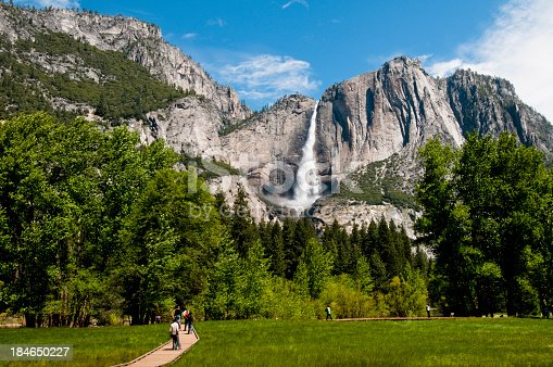 View from the road of Yosemite Waterfall. Unrecognisable people walking along the path in-front of it.