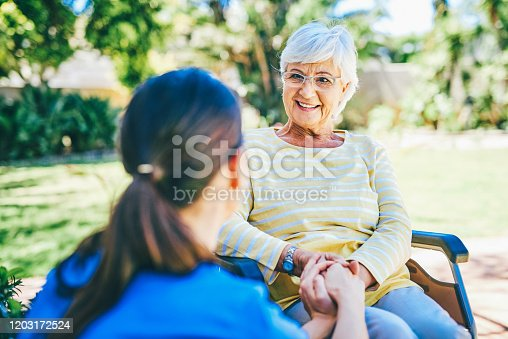 Cropped shot of a senior woman smiling while talking to a female nurse outdoors at a nursing home