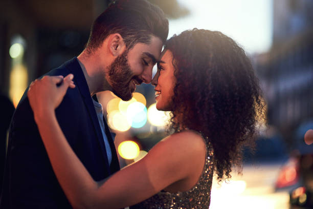 You and me against the world Shot of a cheerful young couple holding one another while looking into each other's eyes outside at night date night romance stock pictures, royalty-free photos & images